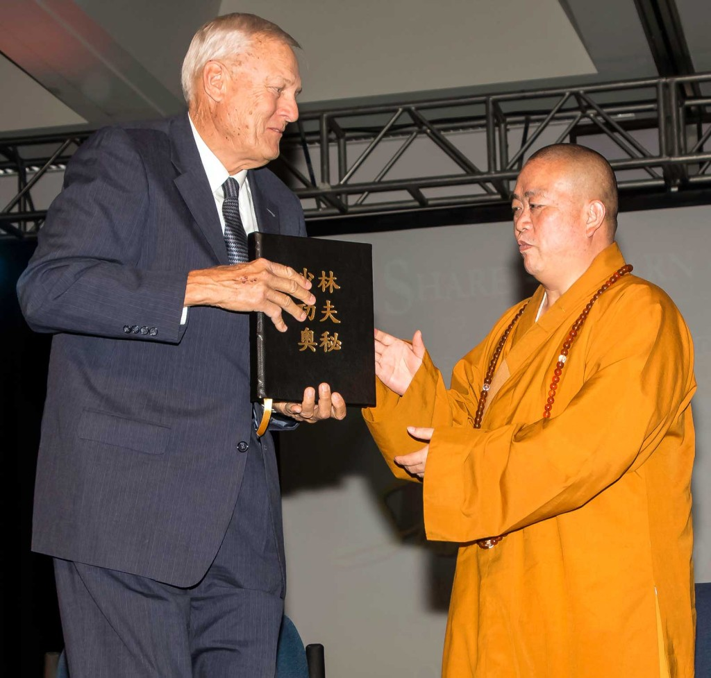 """Board of Trustees member Dr. Gary Cunningham, left, gives Shaolin Temple Abbot Shi Yongxin a hand-made book of the """"Philosophy of Shaolin Kung Fu"""" course translated into Chinese."""